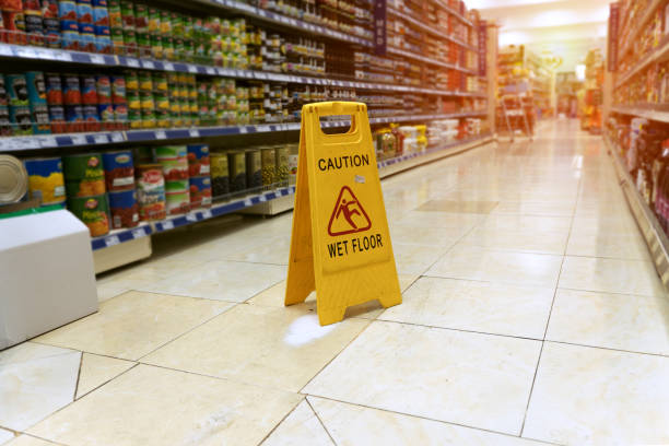 close up Yellow sign - caution. Wet floor is in the supermarket against the background of blurry products standing on the shelves falling stock pictures, royalty-free photos & images