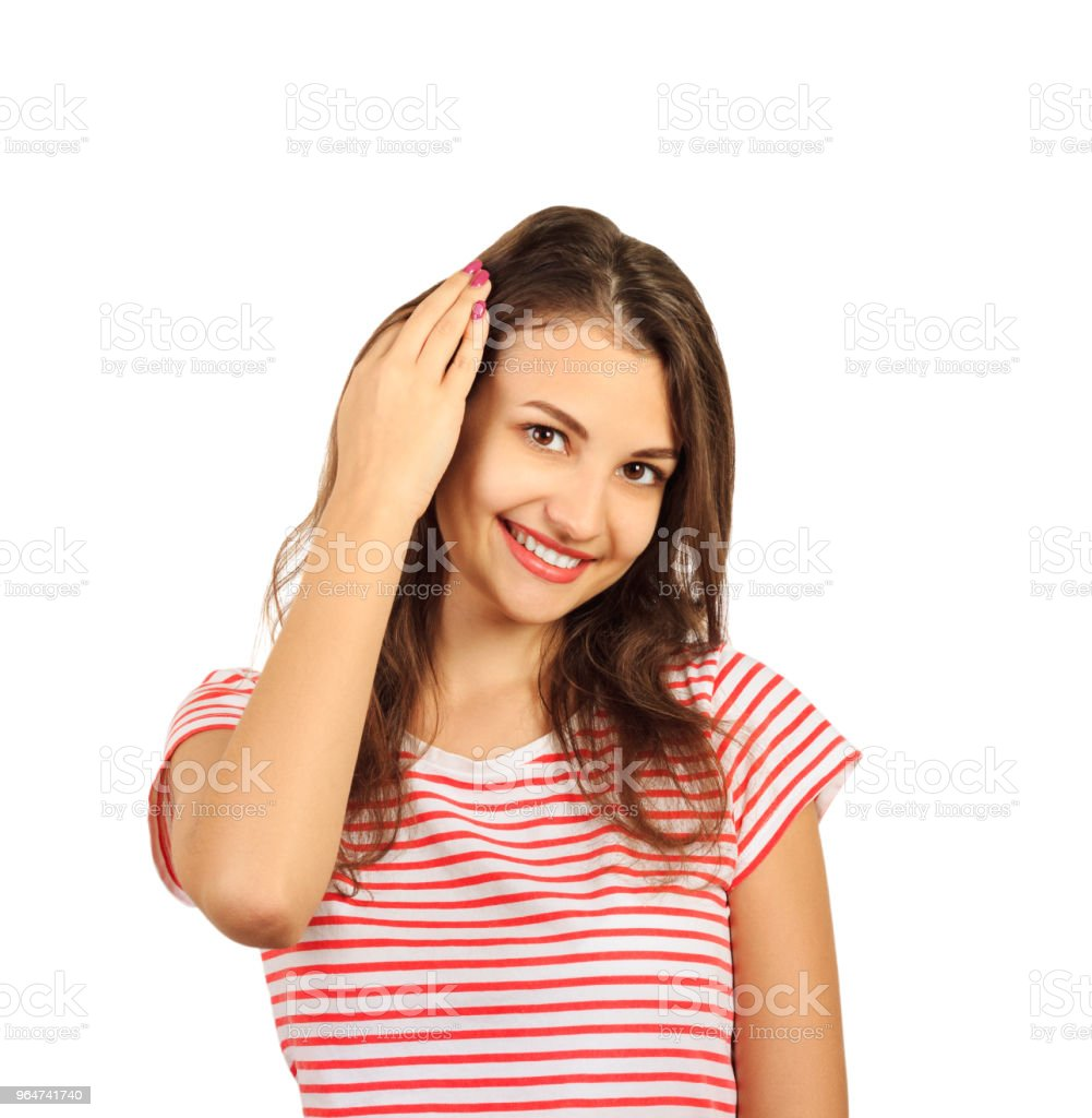 Close up picture of a young beautiful woman fixing her hair while looking at the camera. emotional girl isolated on white background royalty-free stock photo