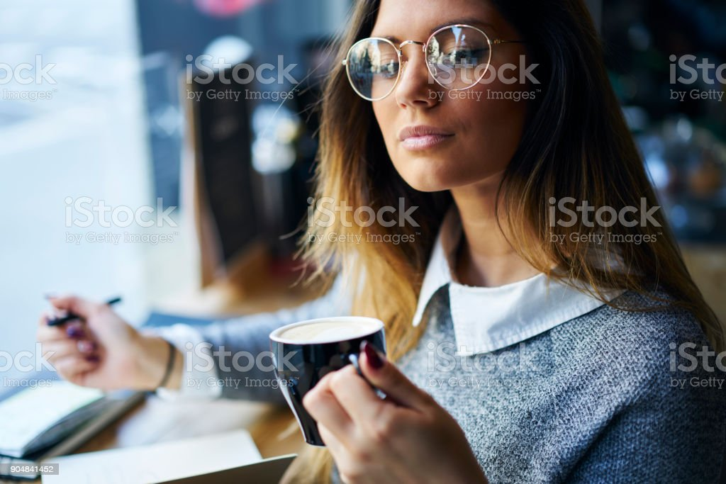 Close up picture of attractive female author in trendy eyeglasses enjoying drinking tea retreating in cozy cafe interior, professional journalist making coffee break while having working process stock photo