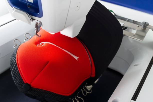 Close up picture of working embroidery machine and red cap stock photo