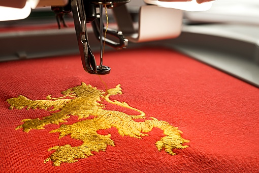 Close up picture of workspace embroidery machine and gold lion design on red fabric in th e hoop copy space on the right