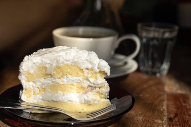 close up piece of coconut chiffon cake on wooden table with warm morning sun light - pandan składnik zdjęcia i obrazy z banku zdjęć