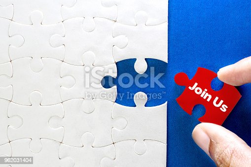 istock Close up piece of white jigsaw puzzle with Join Us text , concept of a business challenge success completion with teamwork 962031404