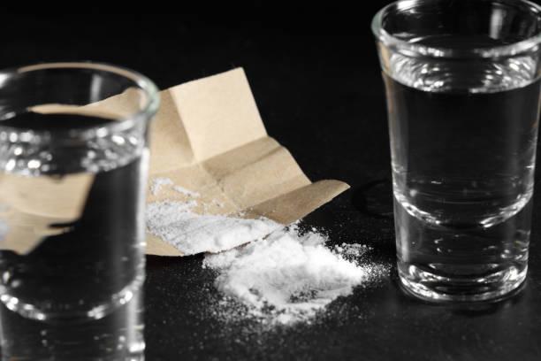 close-up stapel cocaïne in papier en wodka op zwarte achtergrond - amfetamine stockfoto's en -beelden