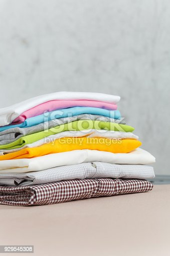 932671892 istock photo Close up pile of ironing colorful clothes, washed laundry, family clothing on ironing board isolated on white background. Housekeeping concept. Copy space for advertisement. With place for text. 929545308