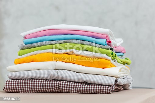 932671892 istock photo Close up pile of ironing colorful clothes, washed laundry, family clothing on ironing board isolated on white background. Housekeeping concept. Copy space for advertisement. With place for text. 936818710