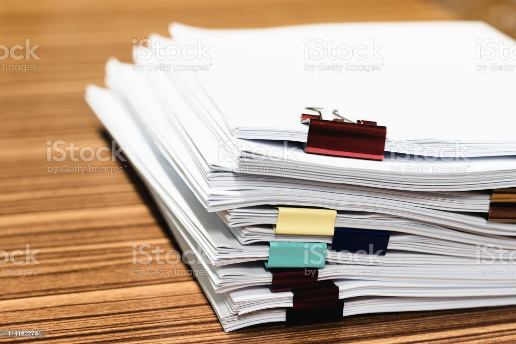 Close up pile of unfinished paperwork on office desk waiting to be...