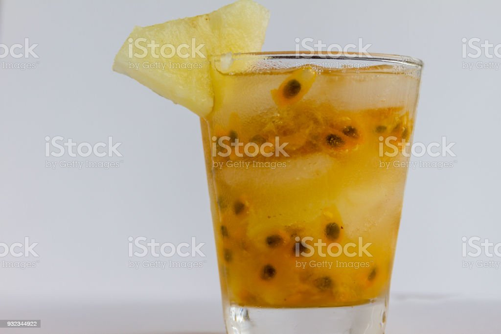 Glass of mixed fruits drink, ice cube, passion fruit and pineapple....