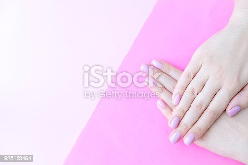 1128559926 istock photo Close up pink nails for girls. Stylish trendy female manicured fingernails. Beautiful young woman's hands on pink and blue background. Top view, flat lay. copy space for text 925183464