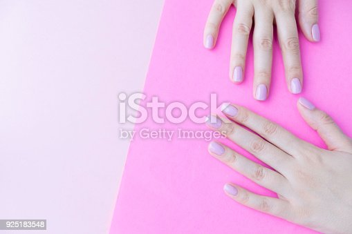 1128559926 istock photo Close up pink nails for girls. Stylish trendy female manicured fingernails. Beautiful young woman's hands on pink and blue background. Top view, flat lay. copy space for text 925183548
