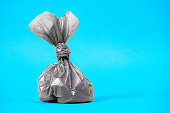 istock Close up plastic bag gathering with dog poop droppings on a blue background. Eco friendly solution for pet owners 1251572816