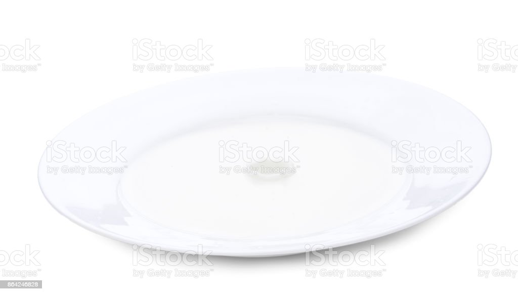 Close up plate with milk, and milk splash. Horizontal close-up image, isolated over white royalty-free stock photo