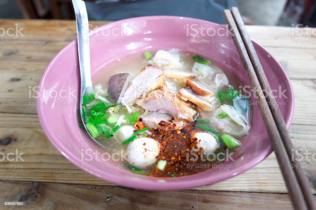 Close up Pork Hot Noodles with Dumpling Thai Style in Pink Ceramic Bowl on Wood Table stock photo