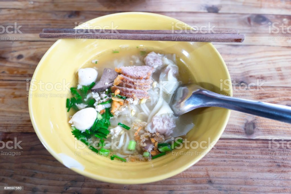 Close up Pork Hot Noodles with Dumpling Thai Style in Yellow Ceramic Bowl on Wood Table stock photo