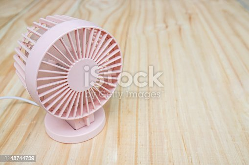 istock close up portable USB fan on wooden frame for cool temperature 1148744739