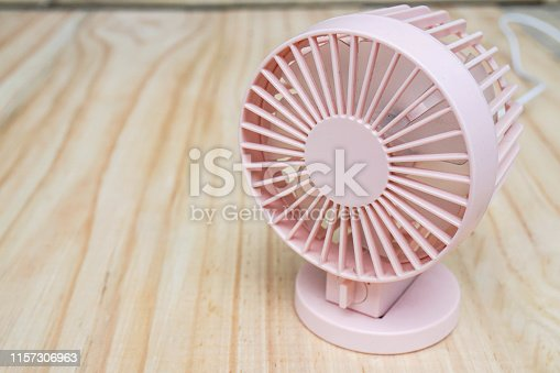 istock close up portable USB fan on wooden frame for cool temperature 1157306963