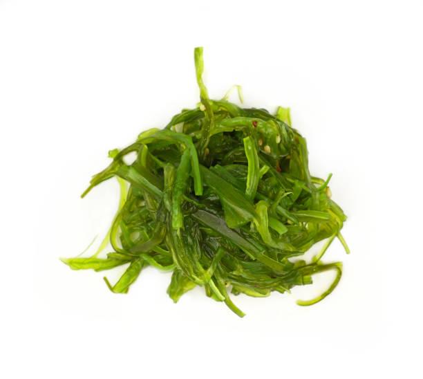 porción de ensalada de algas wakame verde de cerca - algas fondo blanco fotografías e imágenes de stock