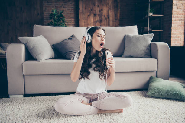 close up portrait beautiful brunette she her lady singing songs having fun free time eyes closed mouth open legs crossed wearing sporty domestic light color t-shirt pants clothes outfit comfy divan - smile woman open mouth foto e immagini stock