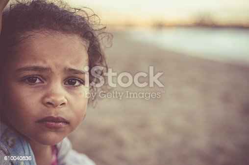 Stock photo of little girl who looks unhappy. She is coming back from a swim in the sea so her hair is wet and she has a towel wrap around her. This file has a signed model release.