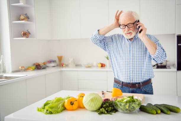 close up portrait grey haired he his him grandpa hold head hand arm telephone smart phone wrong recipe listen new worried wear specs casual checkered plaid shirt jeans denim outfit light kitchen - chef triste foto e immagini stock