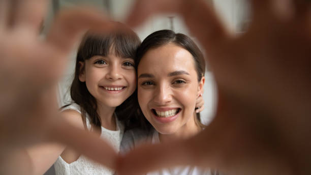 Close up portrait happy family of two making heart gesture. Close up head shot portrait happy family of two making heart gesture, focus on smiling young mother bonding little cute daughter. Overjoyed small girl showing love sign with millennial mommy. young girls on webcam stock pictures, royalty-free photos & images