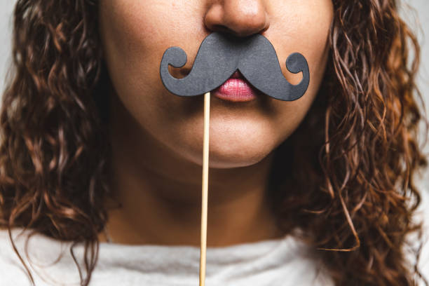 Close up portrait head shot of Young girl wearing fake mustaches - Girl holding funny mustache on stick stock photo