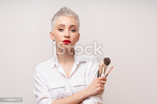 Close up portrait makeup artist. Make up courses. Concept of self visage masterclasess. Fashion professional. Woman hold makeup brushes on the hands. Studio shot on the white background