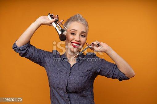 Close up portrait makeup artist. Make up courses. Concept of self visage masterclasess. Woman hold makeup brushes on the hands. Studio shot on the orange color background. Positive people smiling