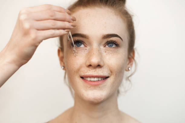 Close up portrait of a beautiful red haired woman applying a transparent serum with hyaluronic acid on her face smiling isolated on white. stock photo