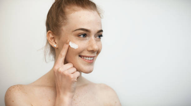 Close up portrait of a beautiful woman with red hair and freckles looking away smiling while applying a white cream on her face isolated. stock photo