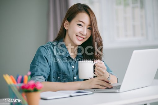 1183295518 istock photo Close up portrait of a beautiful young Asia woman smiling and looking at laptop screen 1249528794