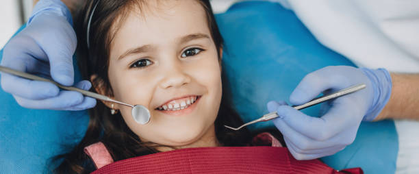 Close up portrait of a caucasian girl having an examination at the pediatric dentist while smiling at camera stock photo