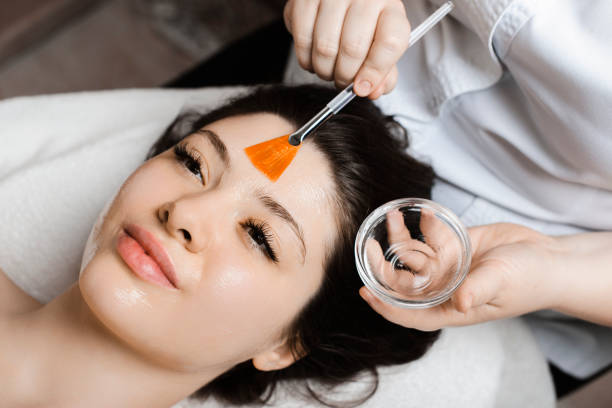 Close up portrait of a charming young female leaning on a spa bed having a mask with hyaluronic acid by a female cosmetologist. stock photo