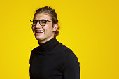 istock Close up portrait of a cheerful young handsome man in black polo neck and eyeglasses laughing joyful over yellow backdrop 1133645491