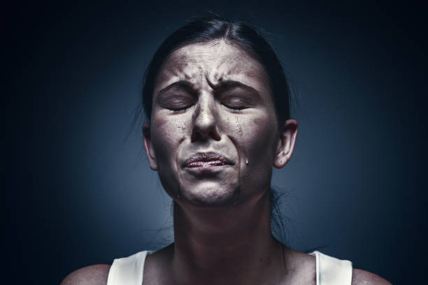 close up portrait of a crying woman with bruised skin and black eyes - fear stock photos and pictures