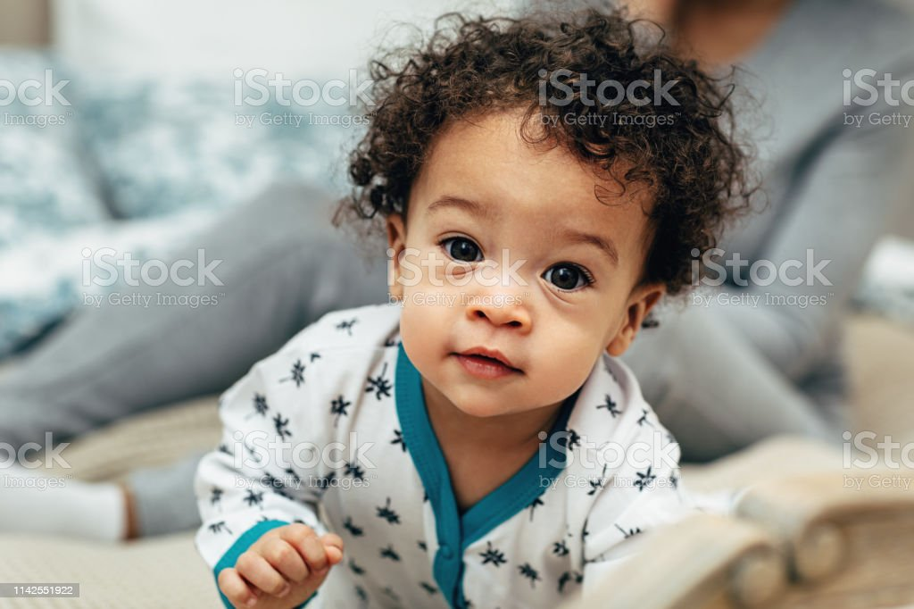 Close Up Portrait Of A Curlyhaired Baby Boy Crawling On ...