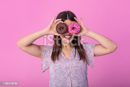 692840848istockphoto Close up portrait of a cute girl posing with donuts at her face isolated over violet background. Beautiful woman with donuts on her eyes 1185416182