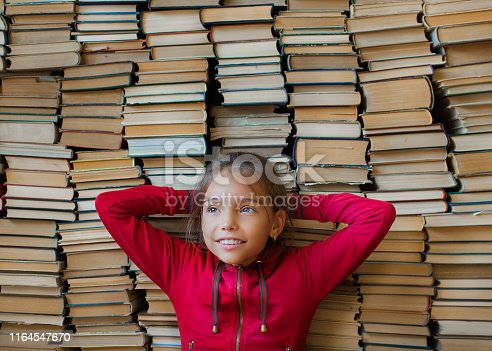 Close up portrait of a dreaming smiling schoolgirl over bookshelf background. Education and school knowledge concept