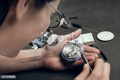 istock Close Up Portrait of a Female Watchmaker at Work 821528590