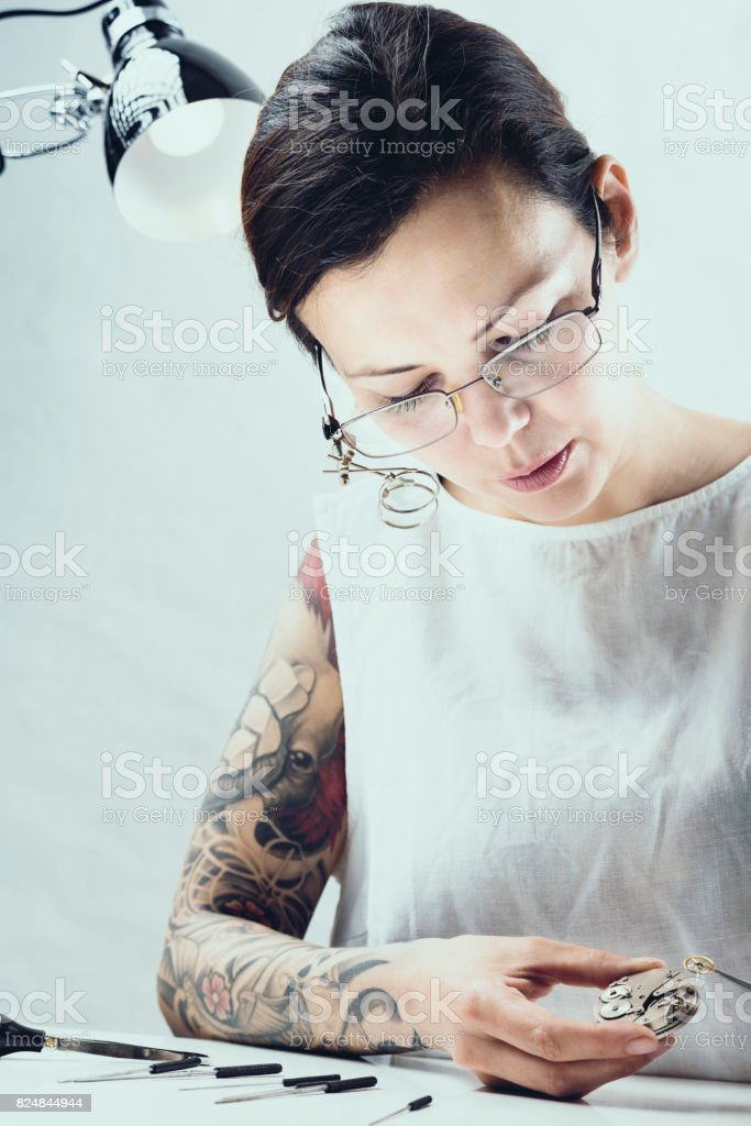 Close Up Portrait of a Female Watchmaker at Work stock photo