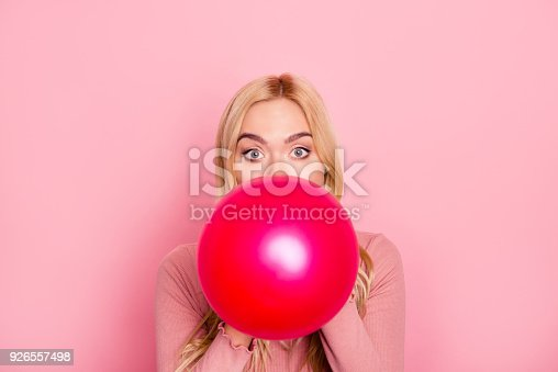 istock Close up portrait of a funny woman inflating a red balloon for party with wide opened eyes and raised eyebrows, standing over pink background 926557498