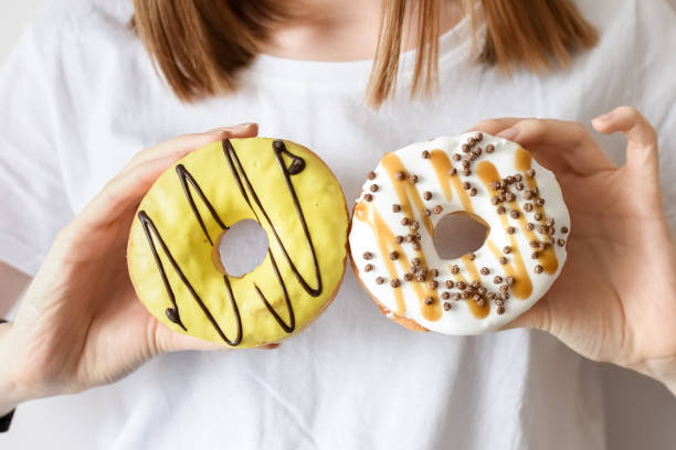 Close up portrait of a girl holding donuts stock photo
