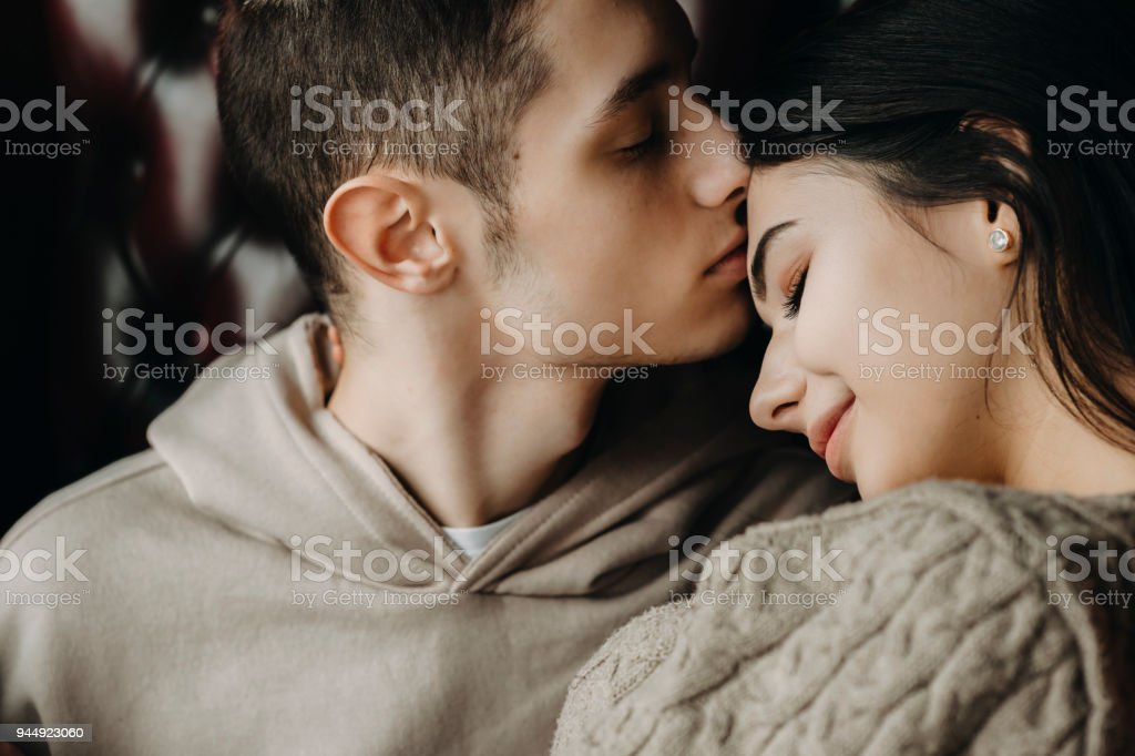 Close up portrait of a lovely young couple sitting on a leather chair while boy is kissing his girlfriend on forehead. stock photo