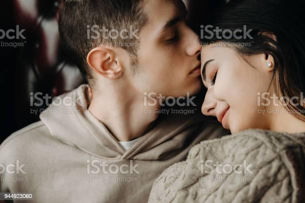 Portret Van Een Mooie Jonge Paar Zitten Op Een Leren Stoel Terwijl Jongen Zijn Vriendin Op Voorhoofd Zoenen Is Closeup Stockfoto en meer beelden van Aanhankelijk