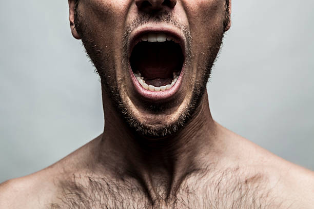 close up portrait of a man shouting, mouth wide open stock photo