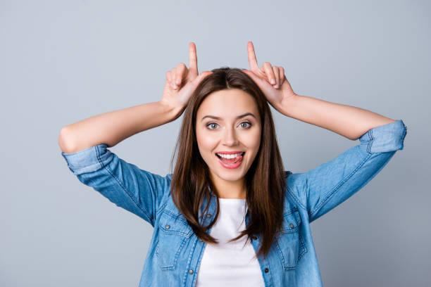 retrato de una muchacha bonita, sonriente de cerca con las manos levantadas sostiene dos dedos como cuernos en la cabeza, mirando muy divertido, mostrando su lengua, de pie sobre fondo gris - maldad fotografías e imágenes de stock