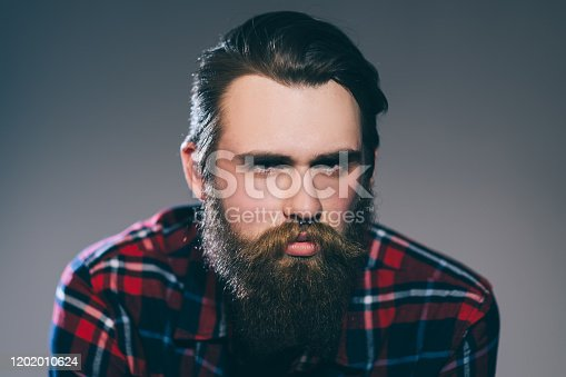 1134770826 istock photo close up. portrait of a stern bearded man in a plaid shirt. 1202010624