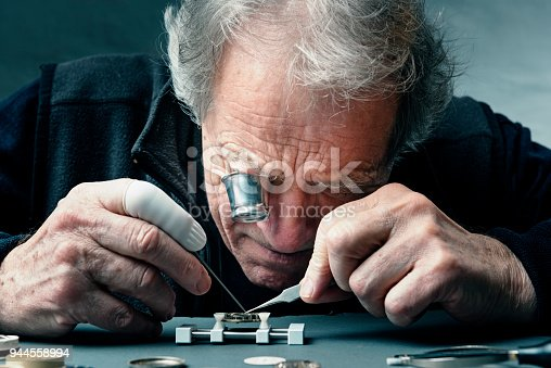 Close up portrait of a watchmaker at work as he carefully repairs the mechanism of a watch. The watch movement is held is a special vice as he works, he is using a magnifying eyepiece to see close up what he is doing. Colour, horizontal with some copy space.