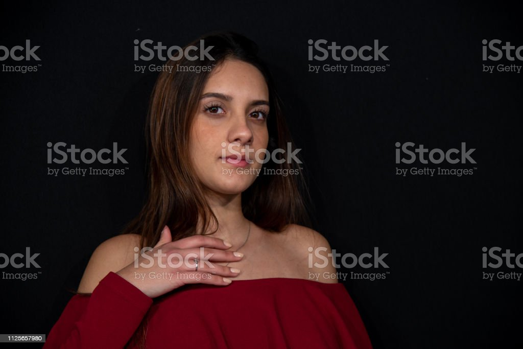 Close up portrait of a young beautiful brunette girl with long hair in studio on black background. stock photo