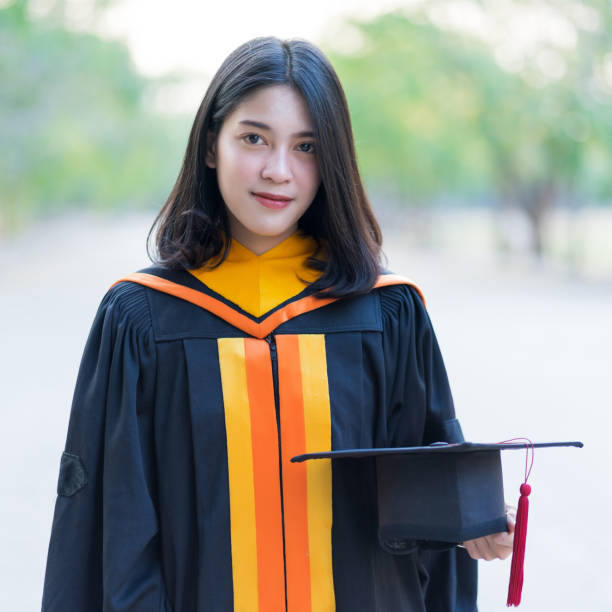 Close up portrait of a young cheerful female graduate wearing academic gown holding graduate cap celebrate her university degree in commence day in college campus. stock photo